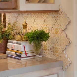 サンディエゴの広い地中海スタイルのおしゃれなキッチン (エプロンフロントシンク、落し込みパネル扉のキャビネット、中間色木目調キャビネット、木材カウンター、ベージュキッチンパネル、モザイクタイルのキッチンパネル、シルバーの調理設備、セラミックタイルの床、ベージュの床) の写真