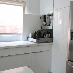 他の地域の中サイズのモダンスタイルのおしゃれなキッチン (アンダーカウンターシンク、フラットパネル扉のキャビネット、白いキャビネット、クオーツストーンカウンター、白いキッチンパネル、シルバーの調理設備の、クッションフロア) の写真