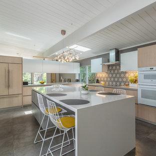 Ispirazione per una cucina minimalista con lavello sottopiano, ante lisce, ante in legno chiaro, paraspruzzi grigio, paraspruzzi con piastrelle di cemento, elettrodomestici da incasso, pavimento grigio e top bianco