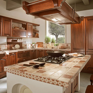マイアミの地中海スタイルのおしゃれなキッチン (レイズドパネル扉のキャビネット、濃色木目調キャビネット、タイルカウンター、マルチカラーのキッチンカウンター) の写真