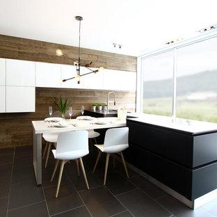モントリオールの中サイズのモダンスタイルのおしゃれなダイニングキッチン (アンダーカウンターシンク、フラットパネル扉のキャビネット、黒いキャビネット、人工大理石カウンター、茶色いキッチンパネル、木材のキッチンパネル、シルバーの調理設備の、セラミックタイルの床) の写真