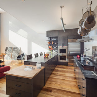 Example of an urban medium tone wood floor open concept kitchen design in Philadelphia with an undermount sink, flat-panel cabinets, metallic backsplash, metal backsplash, stainless steel appliances, two islands and multicolored countertops