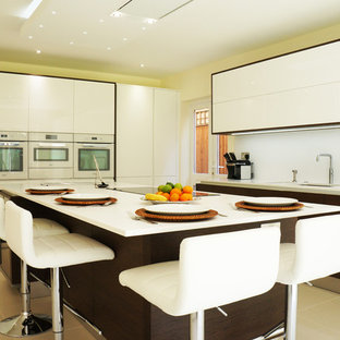 Large midcentury u-shaped kitchen/diner in Surrey with a built-in sink, flat-panel cabinets, white cabinets, composite countertops, white splashback, ceramic splashback, stainless steel appliances, ceramic flooring and a breakfast bar.