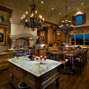 Design ideas for an expansive traditional u-shaped open plan kitchen in Phoenix with dark hardwood floors, glass-front cabinets, distressed cabinets, glass benchtops, black splashback, marble splashback, stainless steel appliances, a farmhouse sink, brown floor, multi-coloured benchtop and multiple islands.
