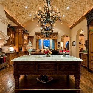 Idéer för ett mycket stort medelhavsstil flerfärgad kök, med en rustik diskho, luckor med glaspanel, skåp i slitet trä, bänkskiva i glas, svart stänkskydd, stänkskydd i marmor, rostfria vitvaror, mörkt trägolv, flera köksöar och brunt golv