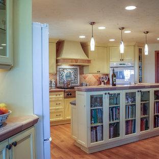 シアトルの大きい地中海スタイルのおしゃれなキッチン (落し込みパネル扉のキャビネット、黄色いキャビネット、タイルカウンター、オレンジのキッチンパネル、セラミックタイルのキッチンパネル、白い調理設備、淡色無垢フローリング) の写真
