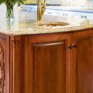 シーダーラピッズの大きいヴィクトリアン調のおしゃれなキッチン (アンダーカウンターシンク、レイズドパネル扉のキャビネット、白いキャビネット、御影石カウンター、マルチカラーのキッチンパネル、石スラブのキッチンパネル、シルバーの調理設備の、磁器タイルの床、ベージュの床) の写真