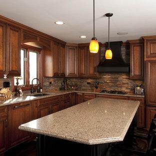 Bild på ett avskilt, mellanstort vintage l-kök, med en undermonterad diskho, luckor med upphöjd panel, skåp i mellenmörkt trä, granitbänkskiva, brunt stänkskydd, stänkskydd i stenkakel, integrerade vitvaror, mörkt trägolv, en köksö och brunt golv