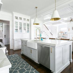 Bild på ett maritimt vit vitt l-kök, med en rustik diskho, skåp i shakerstil, vita skåp, rostfria vitvaror, mörkt trägolv, en köksö och brunt golv