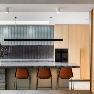 Inspiration for a contemporary galley kitchen in Melbourne with an undermount sink, flat-panel cabinets, light wood cabinets, window splashback, with island and grey benchtop.