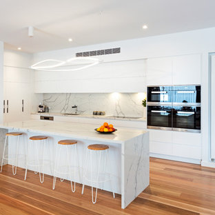 This is an example of a contemporary kitchen in Melbourne with an undermount sink, flat-panel cabinets, white cabinets, white splashback, stainless steel appliances, medium hardwood floors, with island, brown floor and white benchtop.
