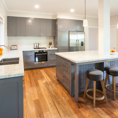 Open concept kitchen - mid-sized traditional l-shaped medium tone wood floor open concept kitchen idea in Melbourne with an undermount sink, shaker cabinets, gray cabinets, granite countertops, beige backsplash, subway tile backsplash, stainless steel appliances, an island and white countertops