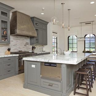 Inredning av ett klassiskt kök och matrum, med grå skåp och stänkskydd i travertin