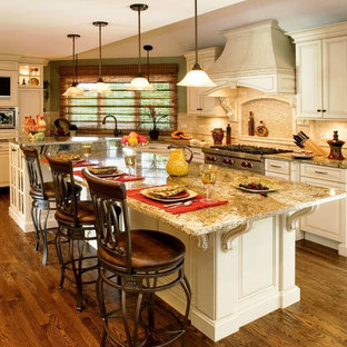 Mid-sized traditional eat-in kitchen ideas - Mid-sized elegant u-shaped medium tone wood floor eat-in kitchen photo in Chicago with an undermount sink, raised-panel cabinets, beige cabinets, granite countertops, beige backsplash, stone tile backsplash, stainless steel appliances and an island
