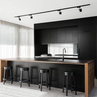 Idéer för ett mellanstort modernt svart kök, med en undermonterad diskho, släta luckor, svarta skåp, spegel som stänkskydd, en köksö, laminatbänkskiva, svarta vitvaror och terrazzogolv