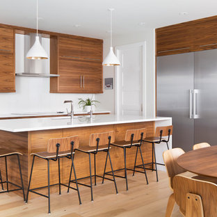 Large midcentury l-shaped open plan kitchen in Calgary with an integrated sink, flat-panel cabinets, medium wood cabinets, white splashback, stainless steel appliances, light hardwood floors, with island, beige floor and white benchtop.