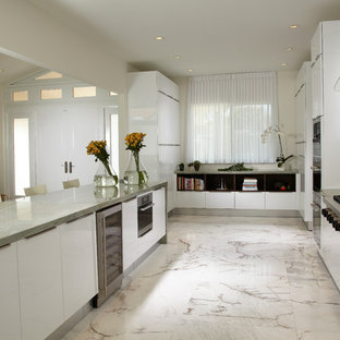 This is an example of a mid-sized contemporary u-shaped open plan kitchen in Miami with an undermount sink, flat-panel cabinets, white cabinets, marble benchtops, glass sheet splashback, stainless steel appliances, marble floors, with island and multi-coloured floor.