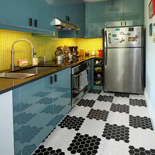 This is an example of a small scandi galley kitchen pantry in New York with a belfast sink, flat-panel cabinets, blue cabinets, glass worktops, green splashback, mosaic tiled splashback, stainless steel appliances, porcelain flooring, white floors and black worktops.