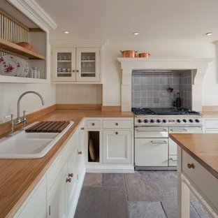 Mid-sized farmhouse kitchen remodeling - Example of a mid-sized farmhouse slate floor kitchen design in London with a farmhouse sink, shaker cabinets, beige cabinets, wood countertops, blue backsplash, ceramic backsplash, white appliances and an island