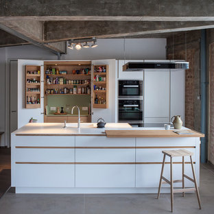 Urban galley open plan kitchen in London with white cabinets, composite countertops, black appliances, an island, an integrated sink and flat-panel cabinets.