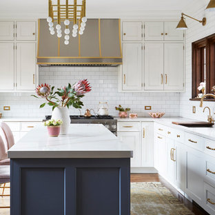 Transitional kitchen ideas - Example of a transitional l-shaped dark wood floor and brown floor kitchen design in Chicago with an undermount sink, shaker cabinets, white cabinets, white backsplash, subway tile backsplash, stainless steel appliances, an island and white countertops