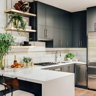 サンフランシスコのコンテンポラリースタイルのおしゃれなキッチン (アンダーカウンターシンク、フラットパネル扉のキャビネット、グレーのキャビネット、クオーツストーンカウンター、白いキッチンパネル、大理石の床、シルバーの調理設備の、無垢フローリング、白いキッチンカウンター、茶色い床) の写真