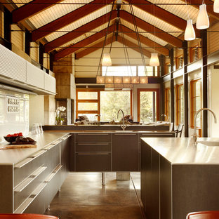 Trendy brown floor open concept kitchen photo in Los Angeles with flat-panel cabinets, brown cabinets, stainless steel countertops, white backsplash and glass sheet backsplash