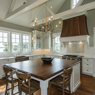 Kitchen - traditional kitchen idea in Charleston with a farmhouse sink, wood countertops, recessed-panel cabinets and white cabinets