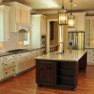 Elegant galley kitchen photo in Charleston with an undermount sink, raised-panel cabinets, beige cabinets, beige backsplash and stainless steel appliances