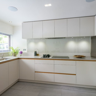 Modern eat-in kitchen ideas - Minimalist l-shaped medium tone wood floor eat-in kitchen photo in London with flat-panel cabinets, white cabinets and no island