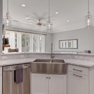 ジャクソンビルの中サイズのビーチスタイルのおしゃれなキッチン (エプロンフロントシンク、シェーカースタイル扉のキャビネット、白いキャビネット、珪岩カウンター、スレートのキッチンパネル、シルバーの調理設備、淡色無垢フローリング、茶色い床、白いキッチンカウンター、グレーのキッチンパネル) の写真