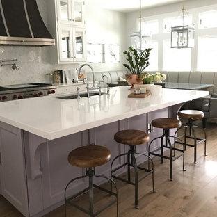 Idéer för mycket stora vintage vitt kök, med en nedsänkt diskho, luckor med profilerade fronter, lila skåp, bänkskiva i kvarts, flerfärgad stänkskydd, stänkskydd i marmor, rostfria vitvaror, mellanmörkt trägolv, en köksö och brunt golv