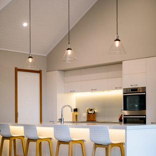 ハミルトンのカントリー風おしゃれなキッチン (フラットパネル扉のキャビネット、白いキャビネット、グレーのキッチンパネル、ガラス板のキッチンパネル、コンクリートの床、グレーの床、白いキッチンカウンター) の写真