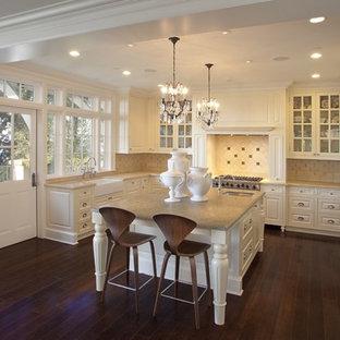 Klassisk inredning av ett kök, med luckor med glaspanel, bänkskiva i kalksten och stänkskydd i kalk