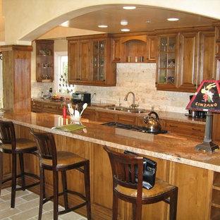 Offene Klassische Küche in L-Form mit Triple-Waschtisch, profilierten Schrankfronten, Schränken im Used-Look, Granit-Arbeitsplatte, Küchenrückwand in Beige, Rückwand aus Steinfliesen und Elektrogeräten mit Frontblende in San Diego