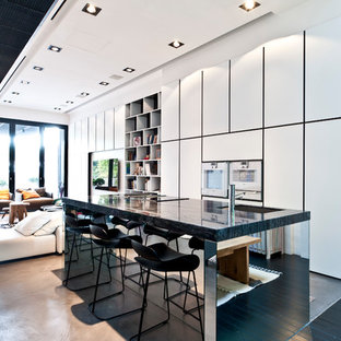 Contemporary open concept kitchen designs - Trendy galley carpeted open concept kitchen photo in Singapore with an undermount sink, flat-panel cabinets, white cabinets, stainless steel appliances and an island