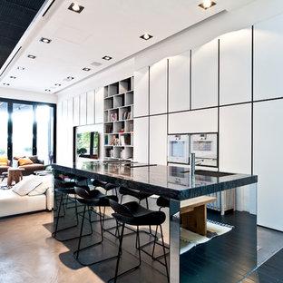 Bild på ett funkis kök, med en undermonterad diskho, släta luckor, vita skåp, rostfria vitvaror, heltäckningsmatta och en köksö