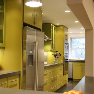 Large contemporary eat-in kitchen remodeling - Eat-in kitchen - large contemporary l-shaped ceramic floor and black floor eat-in kitchen idea in Boston with an undermount sink, flat-panel cabinets, yellow cabinets, concrete countertops, black backsplash, mosaic tile backsplash, stainless steel appliances and a peninsula