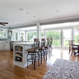 Große Tropische Wohnküche mit gelben Schränken, Küchengeräten aus Edelstahl, Unterbauwaschbecken und hellem Holzboden in Charleston