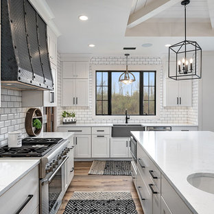 Inspiration for a country l-shaped kitchen pantry in Grand Rapids with a farmhouse sink, shaker cabinets, white cabinets, quartz benchtops, white splashback, ceramic splashback, stainless steel appliances, vinyl floors, with island, brown floor and white benchtop.
