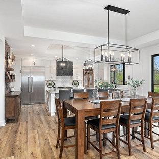 Idéer för lantliga vitt kök, med en rustik diskho, skåp i shakerstil, vita skåp, bänkskiva i kvarts, vitt stänkskydd, stänkskydd i keramik, rostfria vitvaror, vinylgolv, en köksö och brunt golv