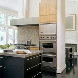 Contemporary open concept kitchen remodeling - Example of a trendy u-shaped painted wood floor and black floor open concept kitchen design in St Louis with flat-panel cabinets, black cabinets, stainless steel countertops, gray backsplash, stone slab backsplash, stainless steel appliances, a single-bowl sink and an island