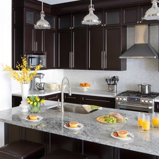 Esempio di una cucina chic con lavello sottopiano, ante in stile shaker, ante in legno bruno, paraspruzzi bianco e elettrodomestici in acciaio inossidabile