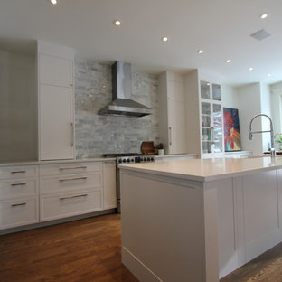 Mid-sized shabby-chic style u-shaped eat-in kitchen in Calgary with a farmhouse sink, flat-panel cabinets, white cabinets, quartzite benchtops, multi-coloured splashback, marble splashback, stainless steel appliances, dark hardwood floors, with island, brown floor and white benchtop.