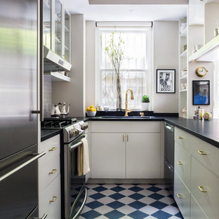 Small traditional enclosed kitchen photos - Small elegant galley porcelain floor and blue floor enclosed kitchen photo in New York with white cabinets, soapstone countertops, white backsplash, porcelain backsplash, stainless steel appliances, no island, an integrated sink and flat-panel cabinets