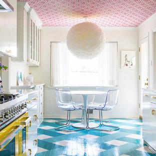他の地域のエクレクティックスタイルのおしゃれなダイニングキッチン (フラットパネル扉のキャビネット、白いキャビネット、カラー調理設備、塗装フローリング、アイランドなし、青い床、白いキッチンカウンター) の写真