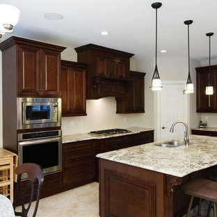 Design ideas for a mid-sized traditional eat-in kitchen with a double-bowl sink, raised-panel cabinets, dark wood cabinets, limestone benchtops, stainless steel appliances, terra-cotta floors and with island.