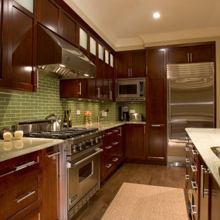 Example of a trendy kitchen design in Chicago with stainless steel appliances, recessed-panel cabinets, dark wood cabinets, granite countertops and green backsplash