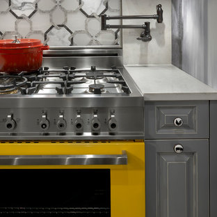 Design ideas for a small eclectic galley separate kitchen in Chicago with raised-panel cabinets, grey cabinets, granite benchtops, white splashback, mosaic tile splashback, coloured appliances, no island, a farmhouse sink and porcelain floors.