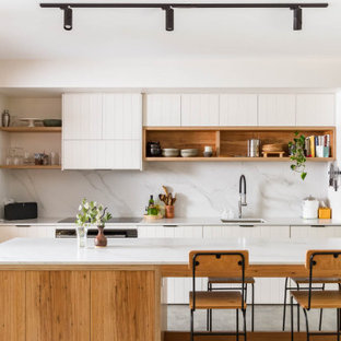 Photo of a transitional u-shaped open plan kitchen in Wollongong with an undermount sink, raised-panel cabinets, white cabinets, grey splashback, black appliances, concrete floors, with island and grey floor.